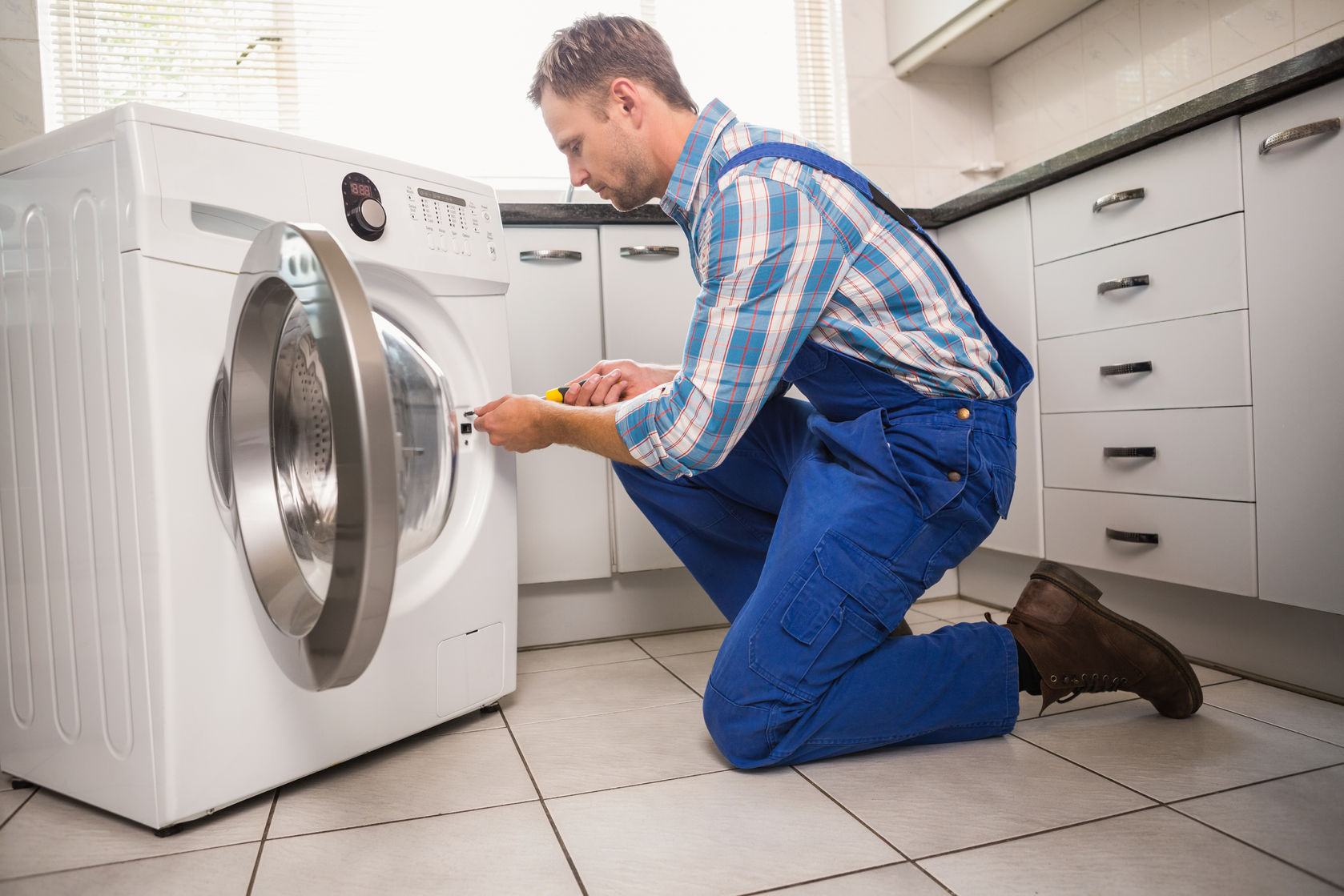 33949789 - handyman fixing a washing machine in the kitchen