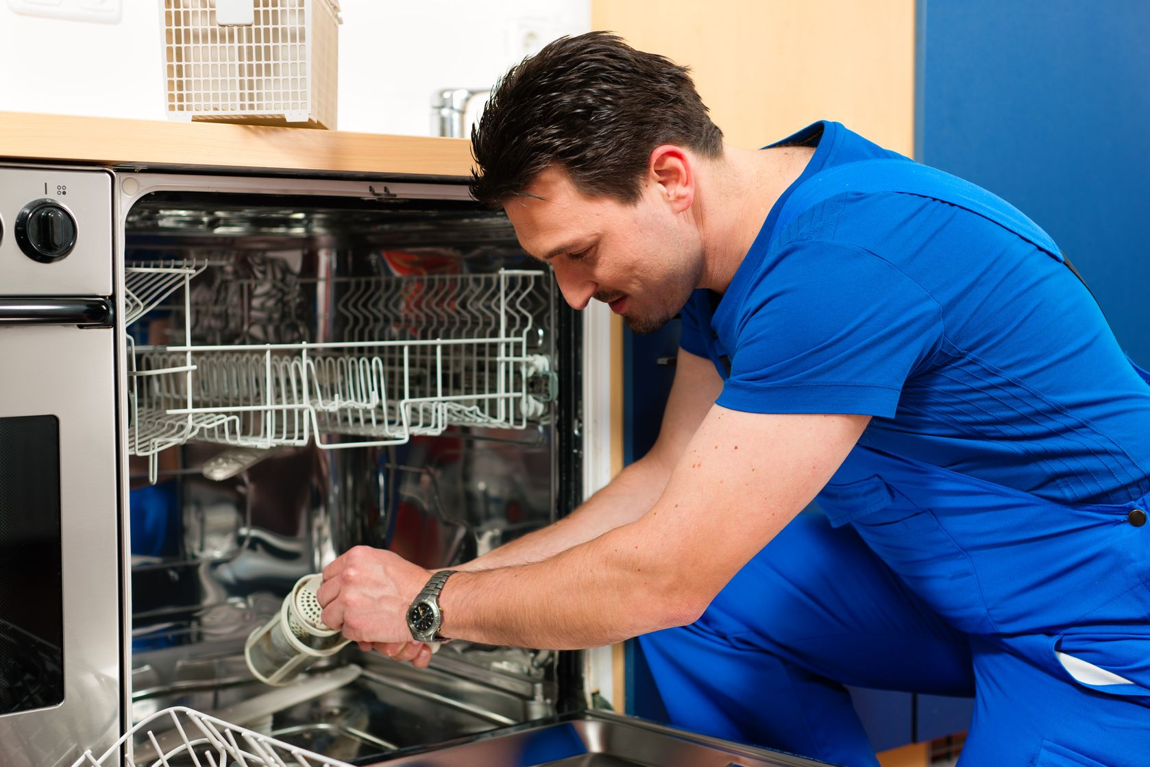 10269956 - technician or plumber repairing the dishwasher in a household