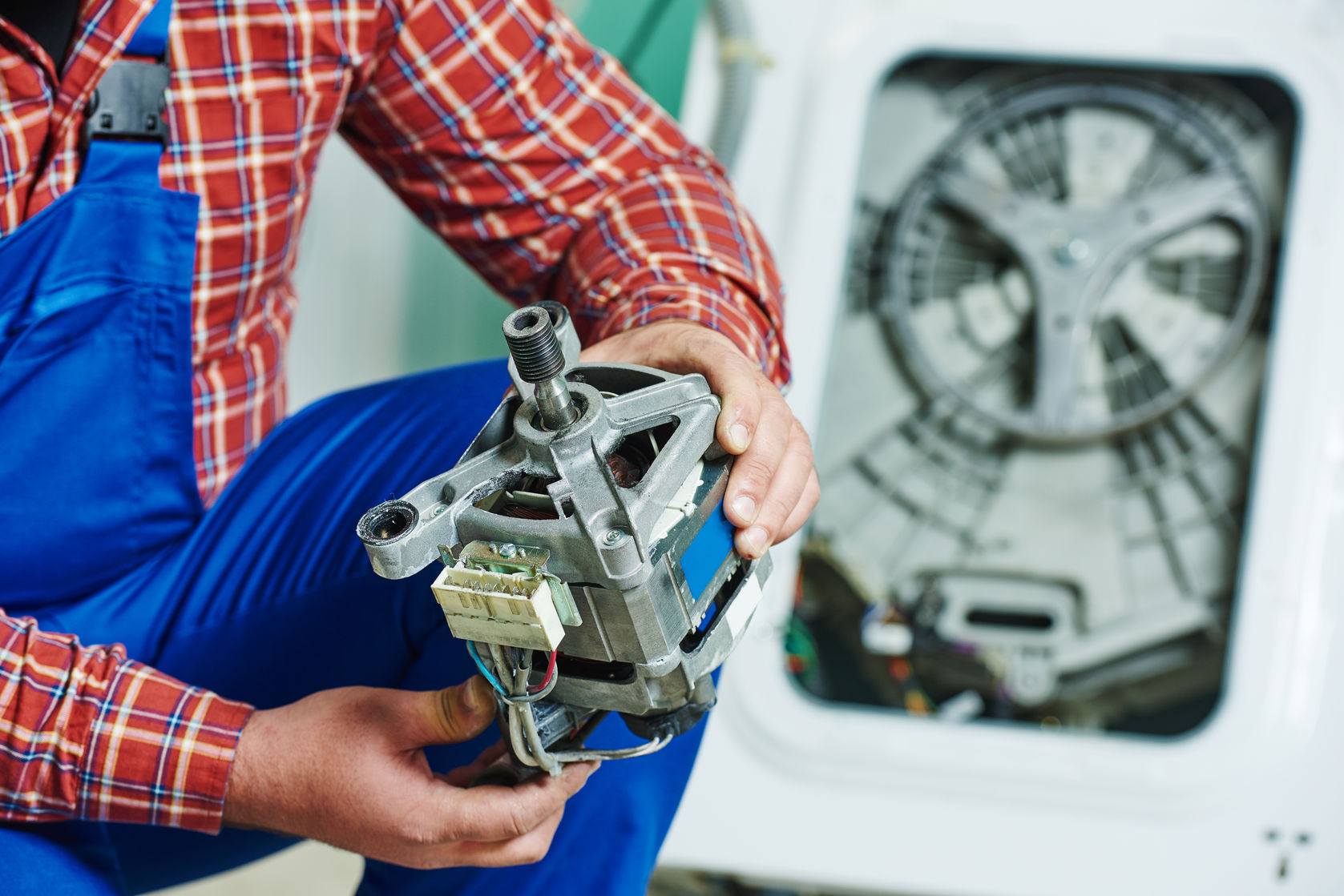 48960142 - washing machine repair. repairer hands with electric engine motor in front of damaged unit
